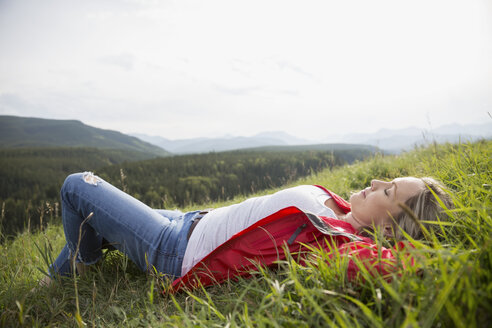 Serene woman laying relaxing with hands behind head in sunny remote rural grass - HEROF13709