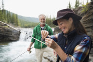 Senior couple fishing at waterfall - HEROF13712