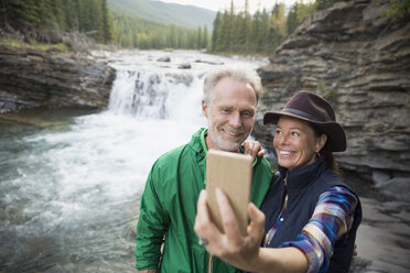 Senior couple taking selfie with camera phone at waterfall - HEROF13715