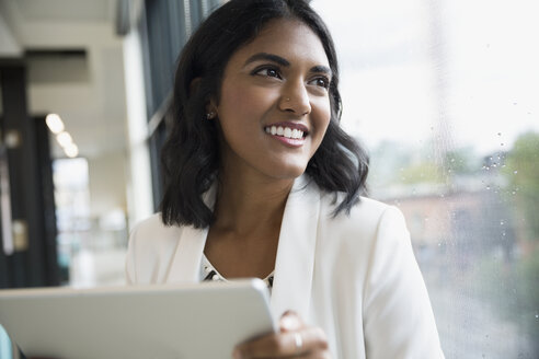 Portrait smiling businesswoman with digital tablet looking out office window - HEROF13730