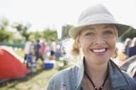 Portrait smiling young blonde woman wearing hat at summer music festival campsite - HEROF13766