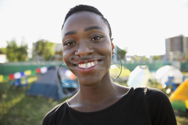 Portrait smiling young woman with black hair at summer music festival campsite - HEROF13769 - Hero Images/Westend61