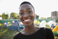 Portrait smiling young woman with black hair at summer music festival campsite - HEROF13769