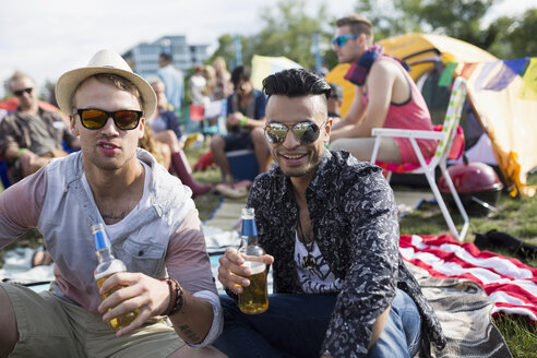 Portrait young men drinking beer at summer music festival campsite - HEROF13781