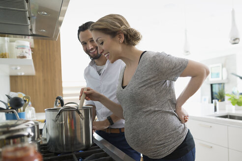 Pregnant couple cooking at stove in kitchen - HEROF13784