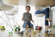 Portrait smiling boy playing with toys under table - HEROF13790