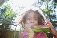 Portrait smiling girl eating watermelon in sunny backyard - HEROF13796