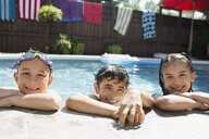 Portrait smiling boys and girl at edge of sunny swimming pool - HEROF13802