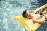 Portrait smiling boy wearing goggles laying on pool raft in sunny swimming pool - HEROF13805