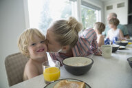 Portrait mother kissing son at breakfast in kitchen - HEROF13826