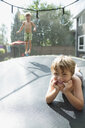 Portrait smiling boys laying and jumping on trampoline in sunny backyard - HEROF13829