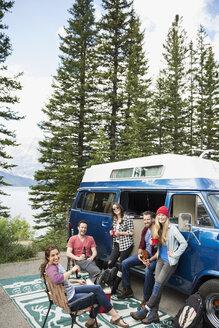 Portrait smiling friends hanging out drinking beer outside camper van at remote lakeside - HEROF13832
