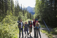 Portrait smiling friends hiking with backpacks and hiking poles on sunny trail in woods - HEROF13835