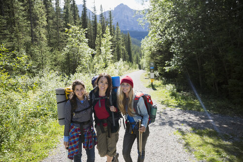 Portrait smiling female friends hiking with backpacks and hiking poles on sunny trail in woods - HEROF13838