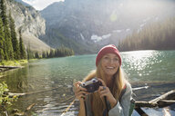 Portrait smiling woman with digital camera at remote sunny mountain lakeside - HEROF13841