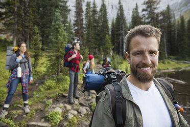 Portrait smiling man with backpack hiking with friends in woods - HEROF13844