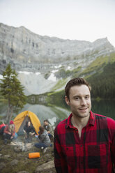 Portrait smiling man at remote mountain lakeside campsite - HEROF13850