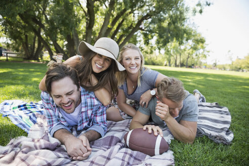 Portrait playful couples laying on blanket in grass in summer park - HEROF13853