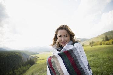 Portrait smiling woman wrapped in blanket in remote rural field - HEROF13856