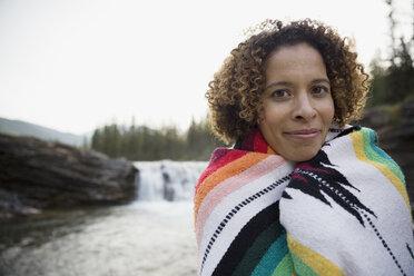 Portrait woman wrapped in blanket near remote waterfall - HEROF13859