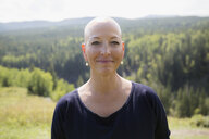 Portrait smiling female cancer survivor with shaved head at sunny remote hilltop - HEROF13862