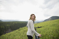 Portrait smiling woman walking mountain bike in remote rural field - HEROF13865