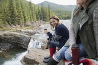 Portrait smiling woman drinking coffee from insulated drink container at waterfall - HEROF13868
