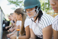 Portrait confident middle school girl softball player wearing batting helmet - HEROF13895