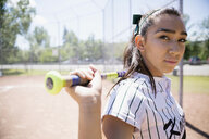 Portrait confident middle school girl softball player holding bat - HEROF13898