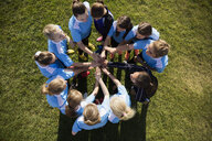 Overhead view middle school girl soccer team joining hands with coach in huddle on field - HEROF13904