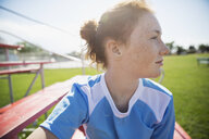 Pensive middle school girl soccer player looking away on sunny bleachers - HEROF13916