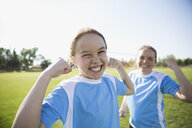 Portrait enthusiastic middle school girl soccer players flexing biceps on sunny field - HEROF13919
