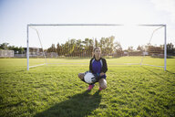 Portrait middle school girl soccer goalie with soccer ball on sunny field - HEROF13928