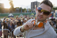 Portrait confident DJ with headphones on stage at summer music festival - HEROF13952