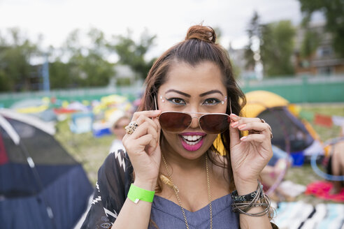 Portrait confident young woman with sunglasses at summer music festival campsite - HEROF13955