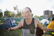 Portrait enthusiastic young man with eyeglasses at summer music festival campsite - HEROF13958