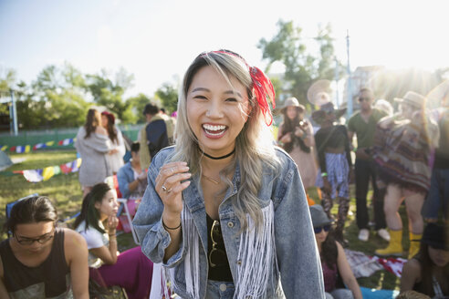 Portrait laughing young woman at summer music festival campsite - HEROF13961