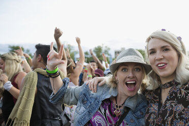 Portrait enthusiastic young women gesturing in crowd at summer music festival - HEROF13964