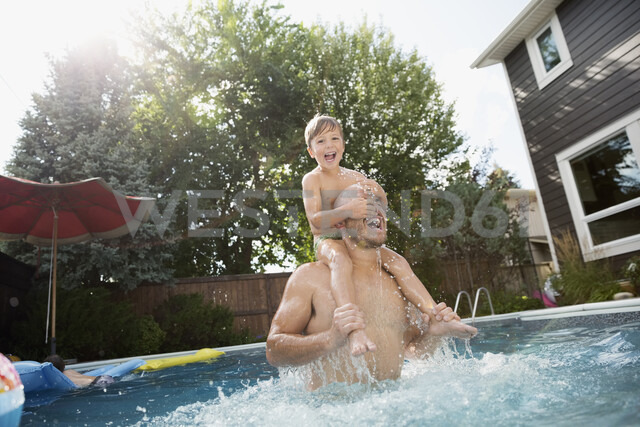 Playful father carrying son on shoulders in sunny swimming pool - HEROF13979 - Hero Images/Westend61