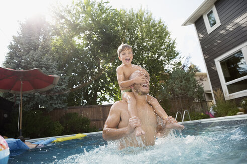 Playful father carrying son on shoulders in sunny swimming pool - HEROF13979
