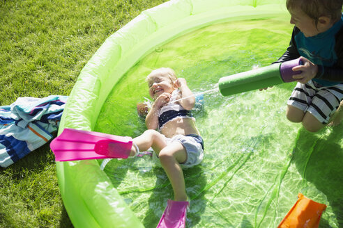 Playful brother spraying sister with squirt gun in sunny wading pool - HEROF13988