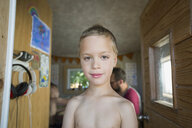 Portrait confident bare chested boy in treehouse doorway - HEROF14006