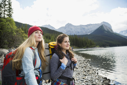 Pensive female friends hiking enjoying remote lake view - HEROF14009