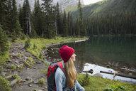 Pensive woman hiking looking at remote lake view - HEROF14012