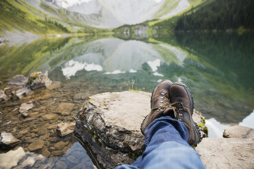 Personal perspective man in hiking boots relaxing with feet up on rocks at remote lake - HEROF14015