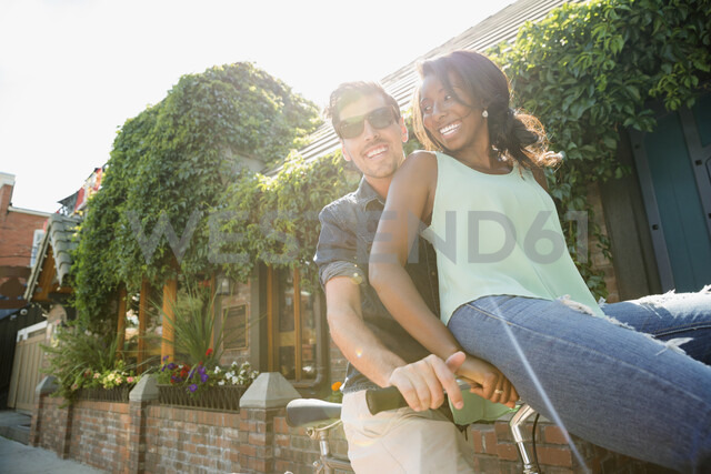 Playful couple riding bicycle on sunny sidewalk - HEROF14030 - Hero Images/Westend61