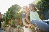 Playful couple riding bicycle on sunny sidewalk - HEROF14030