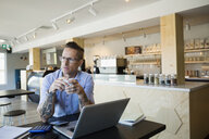 Pensive male cafe owner drinking coffee at laptop - HEROF14036