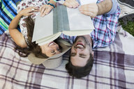 Overhead view couple reading book on blanket in park - HEROF14042