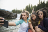 Playful sisters making silly faces taking selfie with camera phone near waterfall - HEROF14048